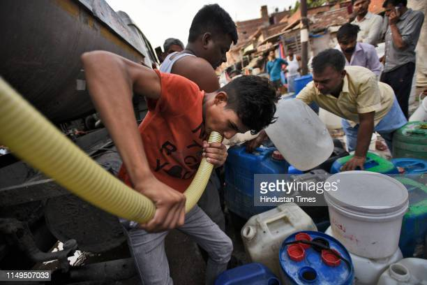 People fill their empty containers with water using lengths of hose pipe from a Delhi Jal Board tanker, at Sanjay Colony in Okhla Phase II, on June...