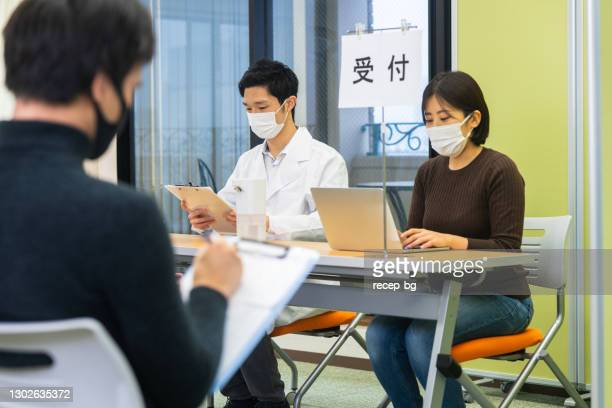 people filling in forms for vaccination - medical receptionist uniforms stock pictures, royalty-free photos & images