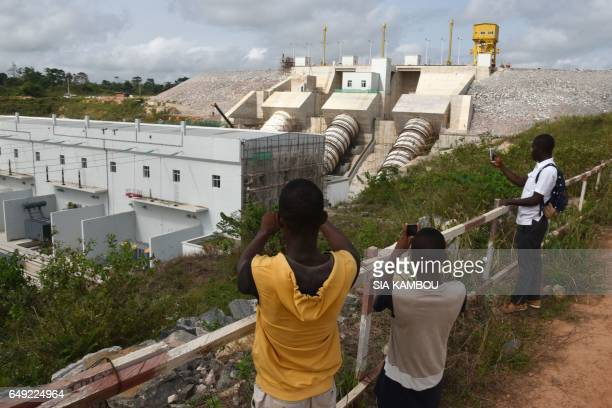 People film the electricity production plant of the Soubre hydroelectric dam with their smartphones on March 6 2017 in Soubre The Soubre...