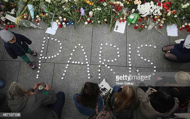People finish arranging candles into the word Paris next to flowers and messages left at the gate of the French Embassy following the recent terror...