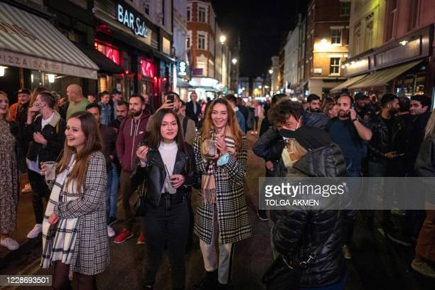 People finish their drinks in the street while the bars are being emptied in Soho, in central London on September 24 on the first day of the new...