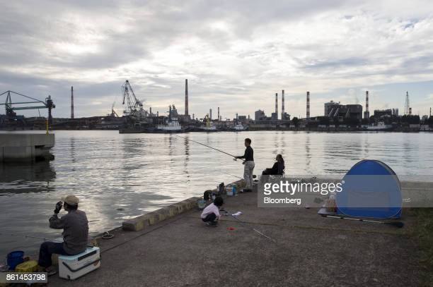 People fish along a promenade as a Kobe Steel Ltd plant stands in the background in Kakogawa Hyogo Japan on Saturday Oct 14 2017 Kobe Steel's fake...