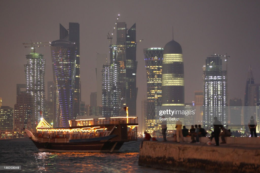 People fish along the waterfront along the Persian Gulf across from new, illuminated financial district skyscrapers as a traditional Arab ship passes by at dusk on October 24, 2011 in Doha, Qatar. Qatar will host the 2022 FIFA World Cup football competition and is slated to tackle a variety of infrastructure projects, including the construction of new stadiums.