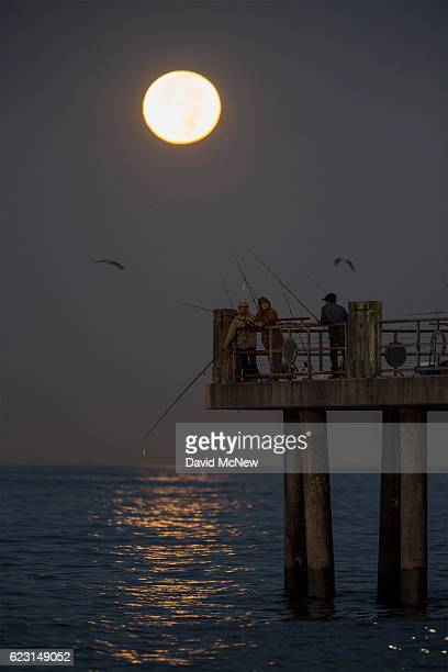 People fish as the moon makes its closest orbit to the Earth since 1948 on November 14 2016 in Redondo Beach California The socalled supermoon...