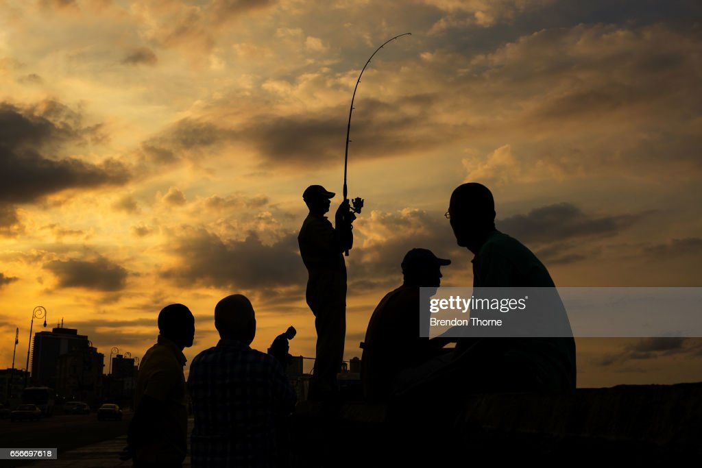 People fish at sunset along the Malecon in Havana on February 2, 2017 in Havana, Cuba.