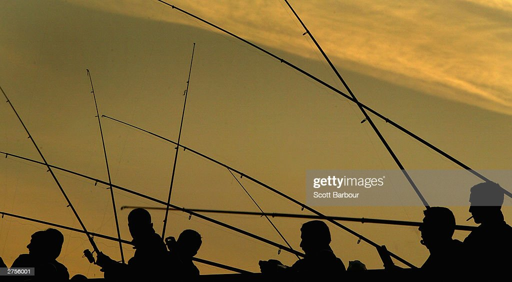 People fish from Galata Bridge as the sun sets November 23, 2003 in Istanbul, Turkey. Daily life is returning to normal after bomb attacks on the British consulate and the HSBC bank headquarters killed 27 people and left hundreds injured last week.