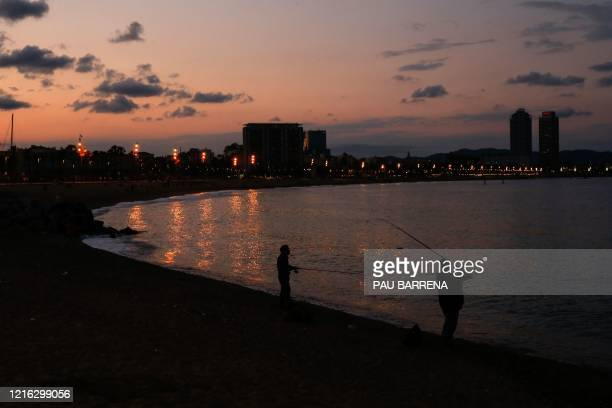 People fish on Barceloneta Beach in Barcelona on May 30, 2020 as the country begins to loosen a national lockdown to prevent the spread of the novel...