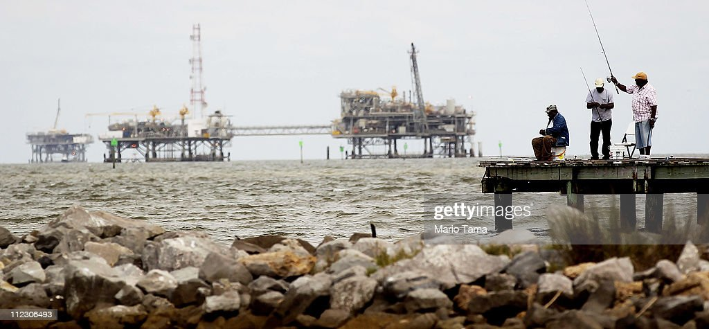 People fish with an oil rig in the background April 18, 2011 in Dauphin Island, Alabama. Dauphin Island's beaches were impacted by oil from the BP oil spill. April 20th marks the one-year anniversary of the worst environmental disaster in U.S. history.