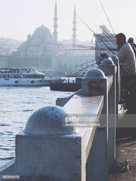 People Fishing At Bosphorus Bridge In Front Of Sultan Ahmed Mosque In City