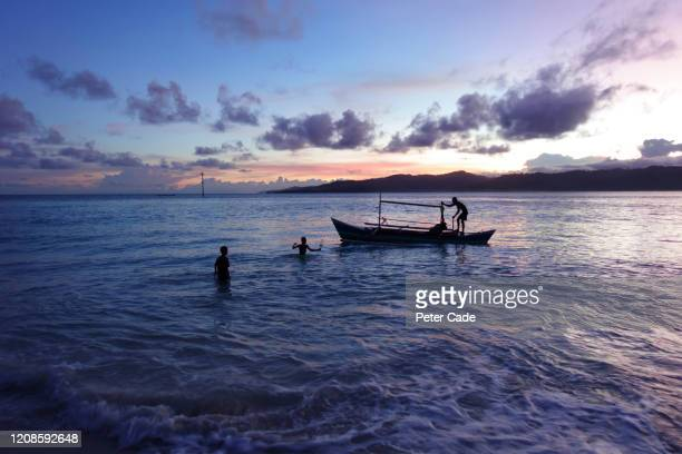 people fishing at sunset from small boat - 発展途上国 ストックフォトと画像