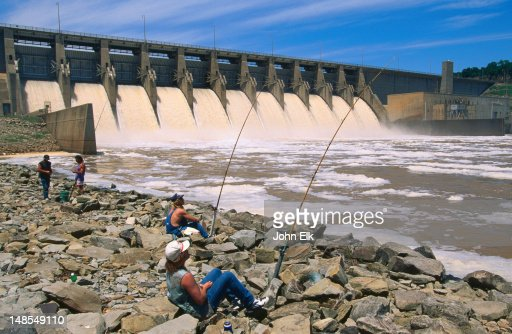 people fishing in lake eufaula dam outflow stock photo