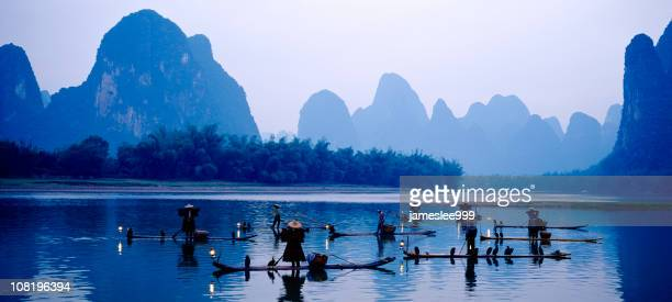 people fishing in the lake near the mountains - yunnan province stock pictures, royalty-free photos & images