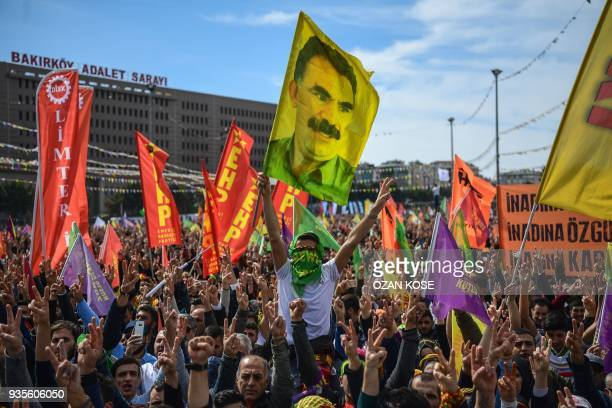 People flash victory sign and wave flags of jailed PKK leader Abdullah Ocalan as part of the Kurdish celebration of Nowruz the Persian calendar New...