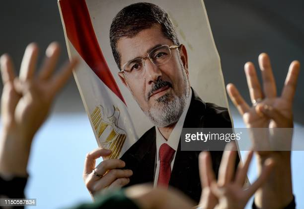 People flashes Rabia sign , next to a poster of former Egyptian President Mohamed Morsi as people attend symbolic funeral ceremony on June 18,2019 at...