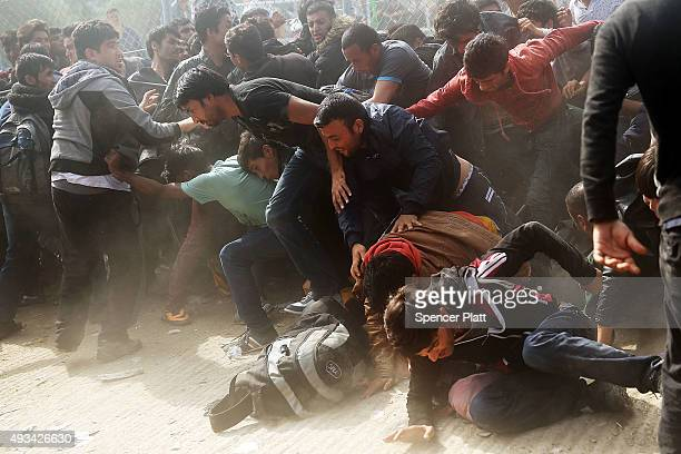 People flee from Afghan men with sticks as they fight with other recently arrived migrants waiting to be processed at the increasingly overwhelmed...