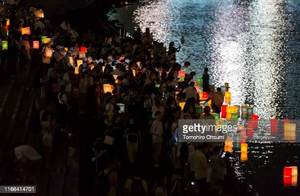 People float candle lit paper lanterns on the river during an event commemorating the 74th anniversary of the atomic bombing of Hiroshima at the...