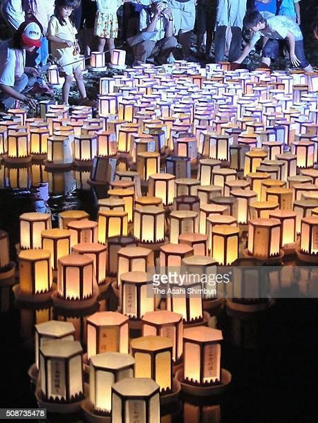 People float candlelit lanterns during the Hikone Manto Nagashi on August 7 2005 in Hikone Shiga Japan 1000 lanterns are floated to pray for ancestors