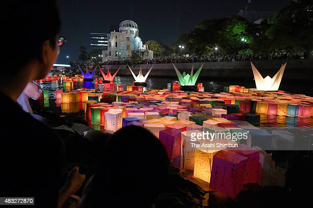 People float candlelit paper lanterns on the Motoyasugawa River on the 70th anniversary of the Hiroshima Atomic Bomb on August 6 2015 in Hiroshima...