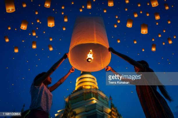 people floating lamp in yi peng festival at chiangmai thailand - tradition stock pictures, royalty-free photos & images