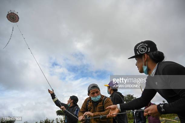 People fly a giant kite during the All Saints' Day commemoration in Santiago Sacatepequez some 48 km west of Guatemala City, on November 1, 2020 amid...