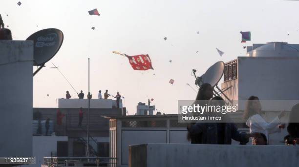 People fly kites from the rooftops of houses on the eve of the Makar Sankranti festival on January 14, 2020 in Jaipur, India.