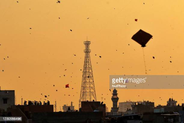 People fly kites on the occasion of 'Makar Sankranti' festival at walled city in Jaipur, Rajasthan, India,Thursday, Jan. 14, 2021.
