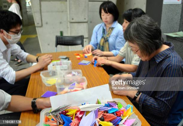 People fold paper cranes to commemorate the victims of the arson of Kyoto Animation studio at Keihan Uji Station on July 25 2019 in Uji Kyoto Japan...