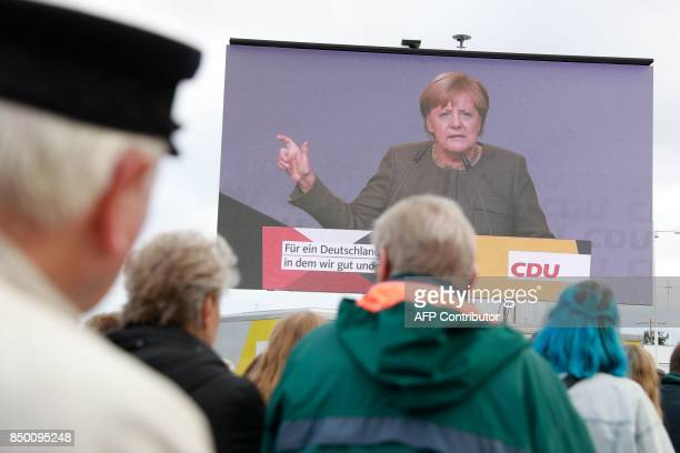 People follow German Chancellor Angela Merkel on a giant screen as she addresses an election campaign rally of the Christian Democratic Union in...
