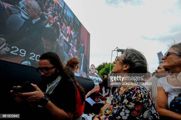 People follow on a giant screen the sentencing hearing for crimes against humanity committed during the last Argentine military dictatorship outside...