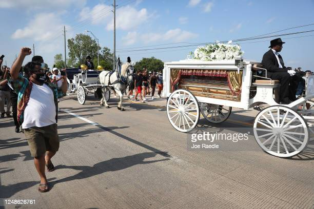 People follow watch as a horsedrawn hearse containing the remains of George Floyd makes its way to the Houston Memorial Gardens cemetery on June 9...
