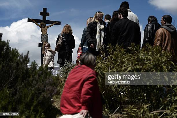 People followers of the Greek Orthodox Church stand in front of an image of Jesus crucified during the ceremony marking the Apokathelosis, the...
