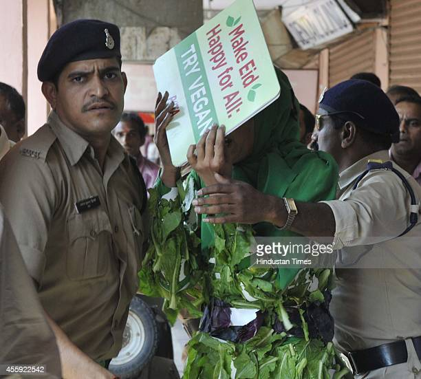 People for the Ethical Treatment of Animals activist who was campaigning for vegetarianism ahead of the Bakrid trying to protect herself behind...