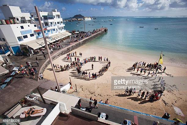 People form a giant SOS on a beach as they protest against oil exploration being carried off the coast of the Canary Islands at a beach of Corralejo...
