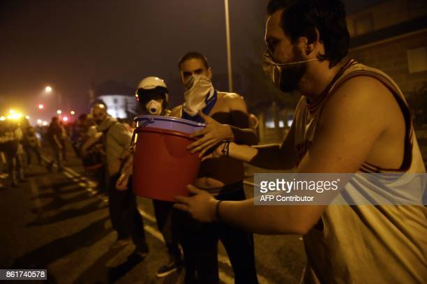 People form a human chain to carry buckets of water to help fighting a wildfire in Vigo northwestern Spain on October 15 2017 Hundreds of...