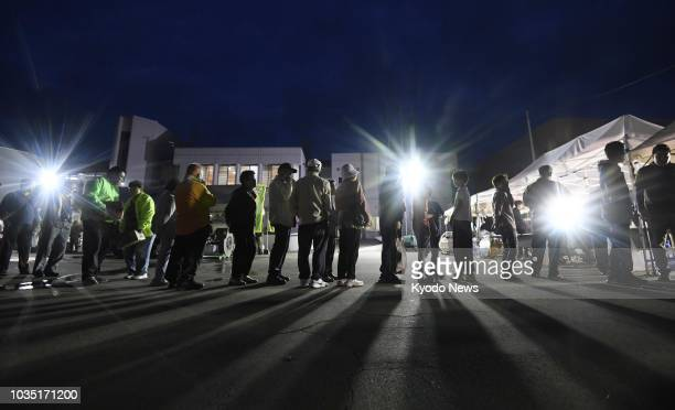 People form a line for a meal at a temporary evacuation center in Atsuma Hokkaido northern Japan on Sept 13 one week after a powerful earthquake hit...