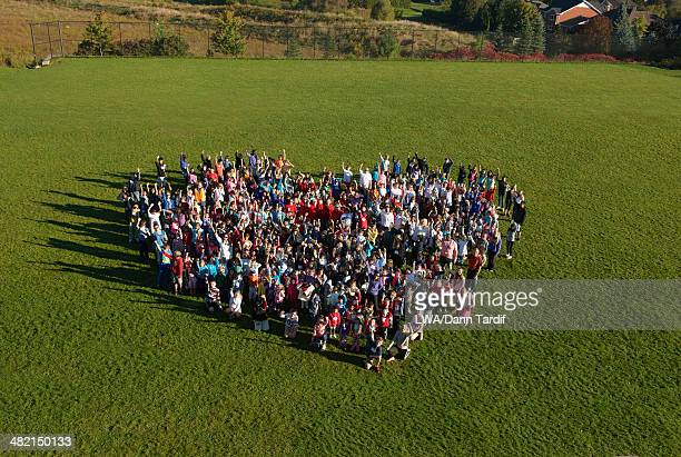 People forming heart-shape in park