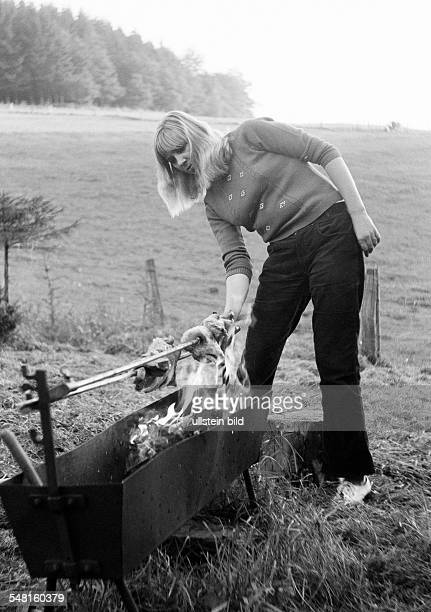 people freetime barbecue in the country young woman turns a roast on the charcoal grill aged 20 to 30 years Kriemhild
