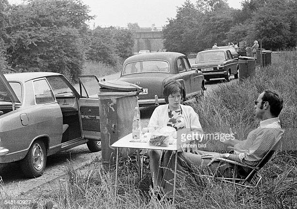People, freetime, young couple takes a rest from motoring in a rest area, aged 25 to 35 years, picnic with folding chairs and a folding table, in the...
