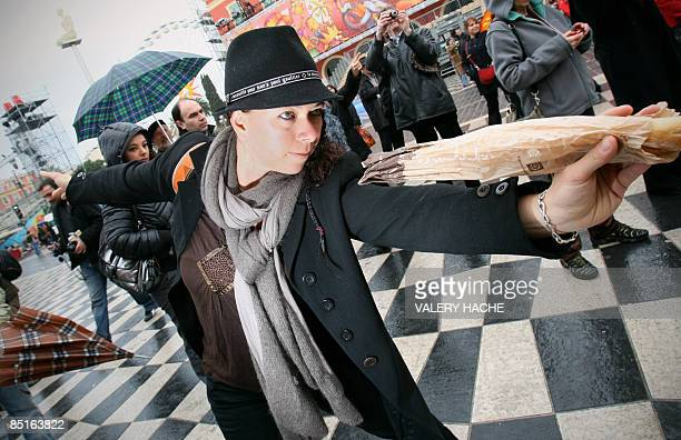 People freeze during a flashmob event during which people pose like a statue during five minutes on March 1st 2009 on the Massena square in Nice...