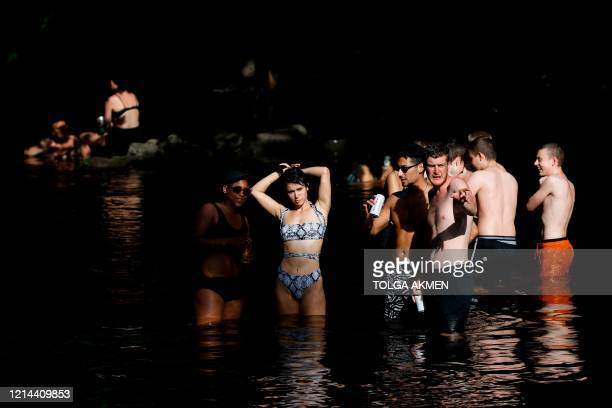 People frolic in the water as they enjoy the sunshine in a park in East London on May 21, 2020. - Hot balmy weather across much of Britain have...