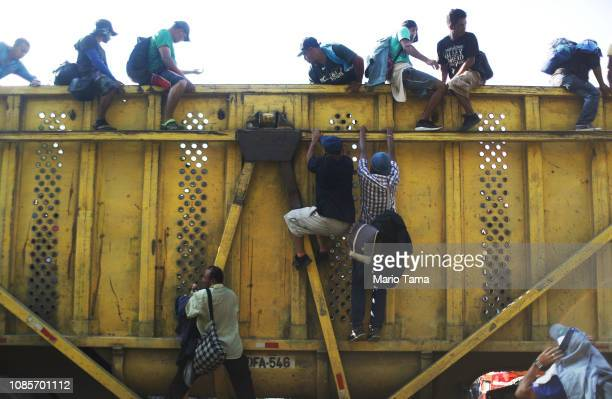 People from a caravan of Central American migrants climb down off a truck they were hoping to catch a ride from on their way to the United States on...