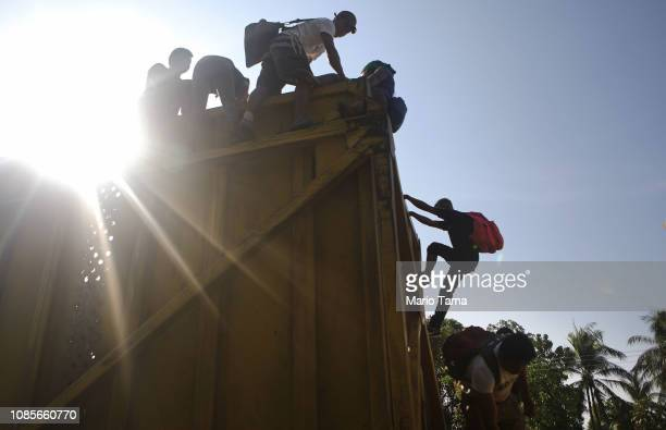 People from a caravan of Central American migrants climb down off of a truck they were hoping to catch a ride from on their way to the United States...