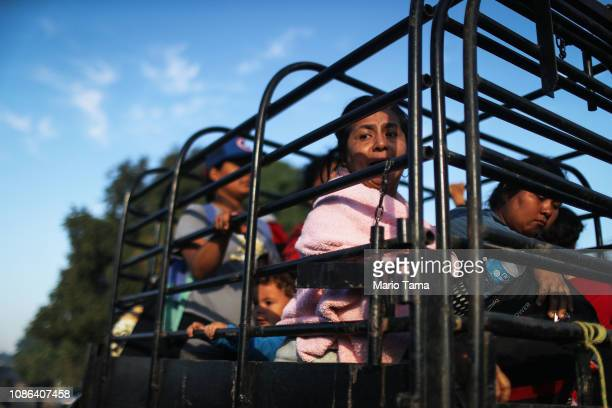 People from a caravan of Central American migrants wait to depart on a truck whose driver offered a ride on their way toward the United States on...
