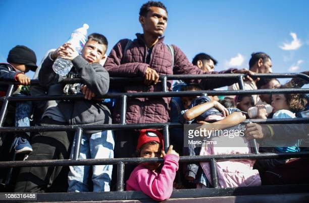 People from a caravan of Central American migrants wait to ride on a truck whose driver offered a ride on their way toward the United States on...