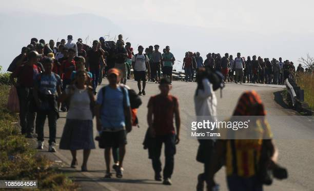 People from a caravan of Central American migrants walk along a roadside on their way to the United States on January 20 2019 in Huixtla Mexico Some...