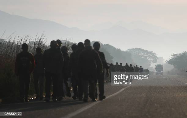 People from a caravan of Central American migrants walk alongside a highway on their way toward the United States on January 22 2019 near Santo...