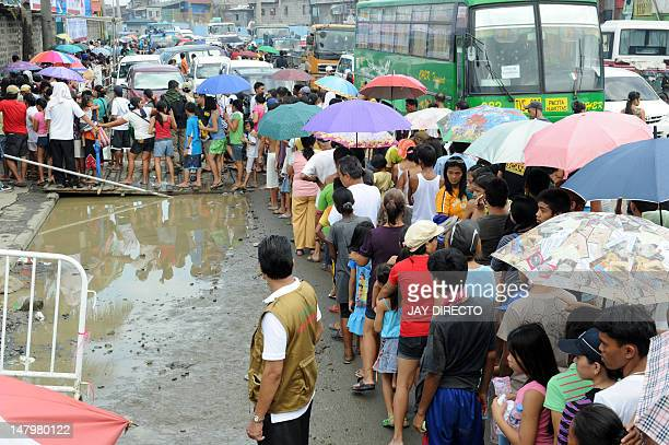 People from a poor area of Manila queue up for free medical treatment at a special aid programme sponsored by a church in the Philippine capital on...