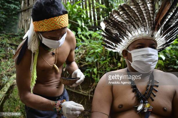 People from an Indigenous community living in the capital of Amazonas Manaus wearing face masks and gloves part of protective measures against the...