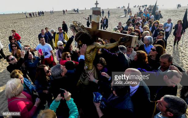 People from Cristo Salvador brotherhood touch an effigy of Jesus Christ during a Holy week procession on April 14 2017 at the beach in Valencia...