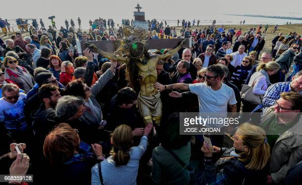 """People from """"Cristo Salvador"""" brotherhood touch an effigy of Jesus Christ during a Holy week procession on April 14, 2017 at the beach in Valencia...."""
